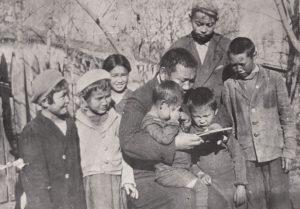 Жусуп читает книгу детям. В светлом берете - дочь Лиля. На коленях - сыновья